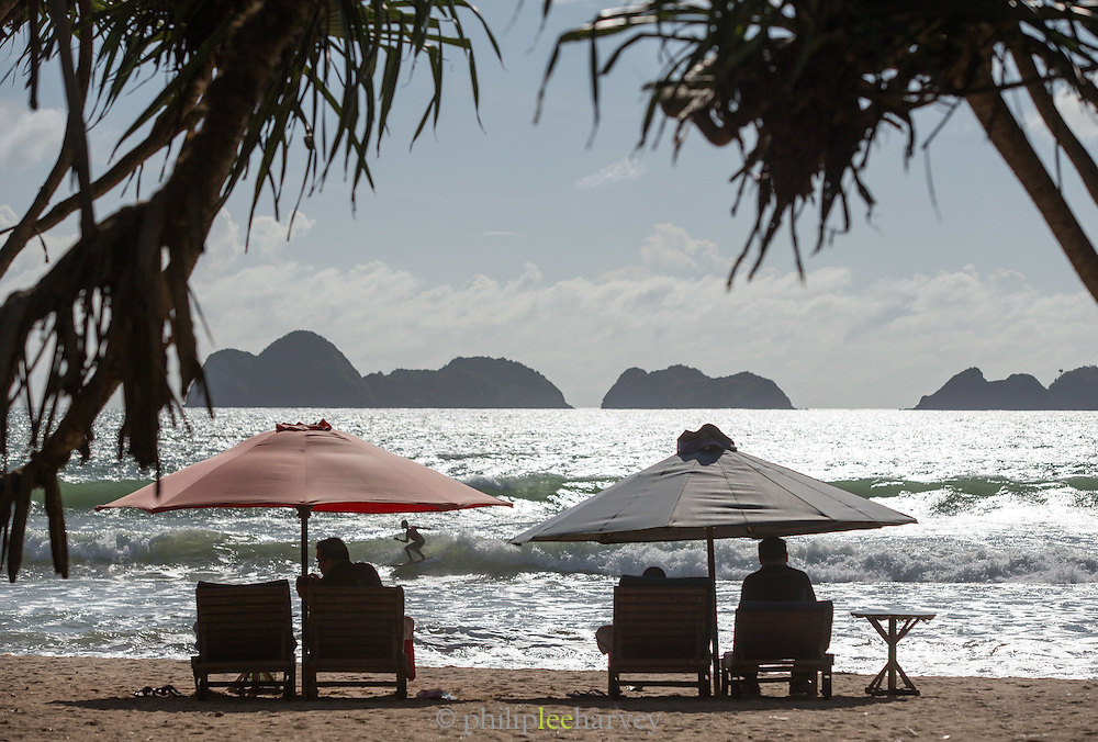 Couple sit on sun loungers beneath umbrella on beach while surfer crosses the waves in front, Red Island Beach, Red Island, Banyuwangi Regency, East Java, Indonesia, Southeast Asia