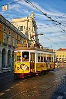 The sun sets on a trolley as it moves through the Praca do Comericio of Lisbon, Portugal