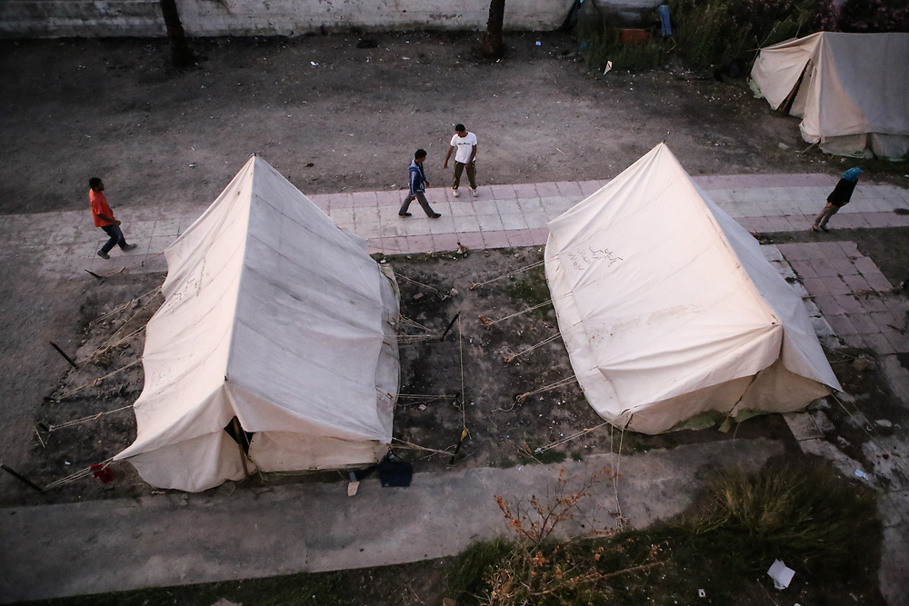 Migrants walk past tents that are used to provide extra shelter at the Hotel Captain Elias in Kos, Greece on July 3, 2015. Doctors Without Borders, an international humanitarian-aid non-governmental organization, set up the tents earlier this year when the greek island of Kos began receiving an influx of migrants and refugees arriving on its shores.