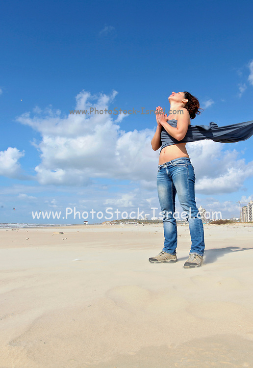 Spiritual young woman communicates with the spirits on a beach
