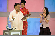 """A presenter smashes Tang Min's (L) family heirloom after it was determined to be a fake on the set of """"Collector's World,"""" a Beijing Television game show. Participants bring their antiques to be appraised by experts and if the articles are deemed to be fakes they are smashed with a golden hammer. The show plays on the country's turbulent modern history, and on the widespread fear of being deceived in a country where everything from DVDs to drugs can be faked."""