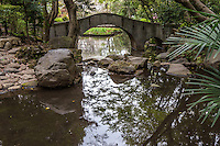 Arched Bridge at Arisugawa-no-miya Park, usually known just as Arisugawa Park contains a lush Japanese strolling garden that follows the hilly contours of the terrain.  The elegantly designed landscape offers  paths with a variety of types of bridges spanning streams that flow into the pond.   Arisugawa-no-miya was originally the domain of feudal lord, then was acquired by the noble Arisugawa-no-miya family. The family donated the land to the city of Tokyo.  Like nearly all Japanese gardens in Tokyo, it is incorporated into a city park.  Within the grounds, occupying a different tier above the pond garden are sports facilities and Tokyo Metropolitan Library Tokyo Torts Toshokan.