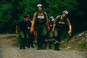 While being shouted and screamed at by a tattooed instructor, a squad of 8 soldier recruits experience the extreme exhaustion and stress during an army team event in which they haul a log (a telegraph pole) weighing 60 kg over 1.9 miles (3.1 km) of undulating terrain. Candidates wear only a numbered helmet and webbing but all their energies must go into performing as a team and completing the course in the time allotted. This is supposed to be one of the hardest events of what the 14-week long Pegasus (P) Company selection programme. Recruits wanting to join the British Army's elite Parachute Regiment held regularly at Catterick army barracks, Yorkshire need to pass this and other tests before earning the right to wear the esteemed maroon beret.