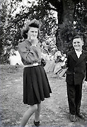 girl and boy holding flowers rural 1950s
