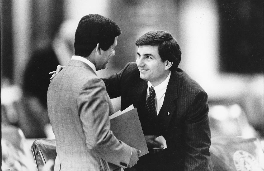 ©1987 Texas House of Representatives:  Rep. Mike Toomey, r, talks with Rep. Hugo Berlanga, D-Corpus Christi.