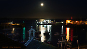 A full moon rises over Penzance Harbour and the Isles of Scilly ferrry the Scillonian. The old lifeboat house can be seen in the foreground.