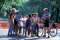 Stock photo of a group of school children and adults outside talking to a bicycle policeman