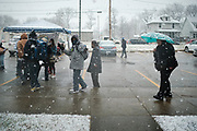 23 NOVEMBER 2020 - DES MOINES, IOWA: People wait for a Thanksgiving food distribution to start at a park in Des Moines during a snowstorm. The food distribution was organized by Urban Dreams, a community empowerment NGO in central Des Moines, and the NAACP. The food was provided by Hy-Vee, a regional grocery store chain based in Des Moines. They had about 450 meals available. A spokesperson for Hy-Vee said the company was giving away more than 20,000 Thanksgiving meals this year. The Food Bank of Iowa said food insecurity in Des Moines has doubled since the start of the Coronavirus pandemic.   PHOTO BY JACK KURTZ