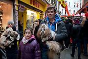 Family of three wih three dogs in Chinatown, London, UK.