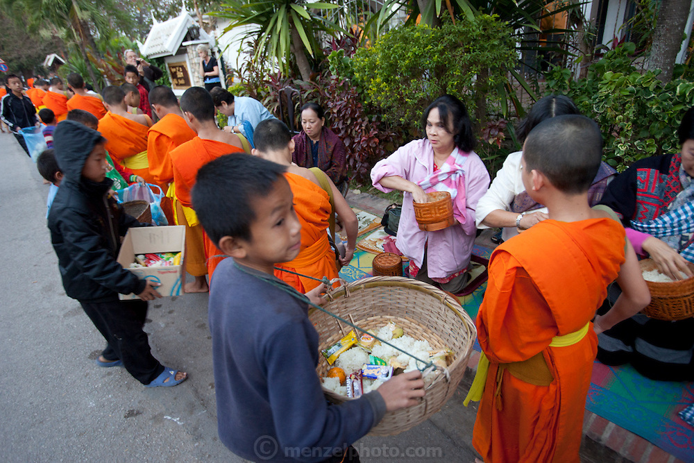 "Luang Prabang, Laos. Every morning at dawn, barefoot Buddhist monks and novices in orange robes walk down the streets collecting food alms from devout, kneeling Buddhists. They then return to their temples (also known as ""wats"") and eat together. This procession is called Tak Bat, or Making Merit."