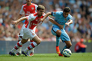Arsenal's Nacho Monreal (l) and (r) Manchester City's Jesus Navas challenging for the ball. Barclays Premier league match, Arsenal v Manchester city at the Emirates Stadium in London on Saturday 13th Sept 2014.<br /> pic by John Patrick Fletcher, Andrew Orchard sports photography.