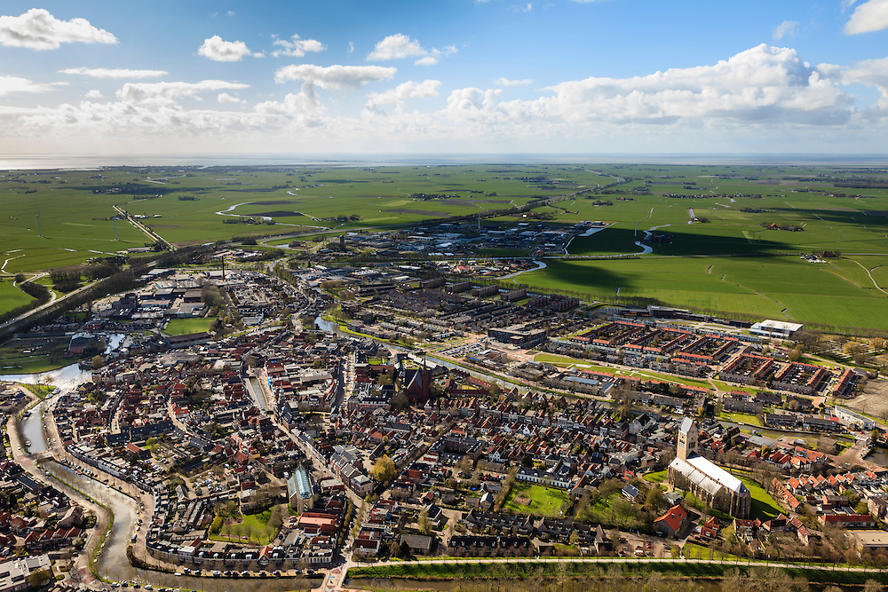 Nederland, Friesland, Gemeente Sudwest-Fryslan, 16-04-2012; Bolsward (Boalsert), gezien naar Afsluidijk (links aan de horizon) en Waddenzee. In het centrum met Broerekerk (links, met glazen dak), Sint-Franciscuskerk (midden, baksteen) en Martinikerk (toren met zadeldak)..Frisian city of Bolsward..luchtfoto (toeslag), aerial photo (additional fee required).foto/photo Siebe Swart