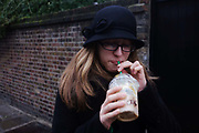 A 15 year-old teenage girl sips a Starbucks Frappuccino coffee through a straw in a London Street. Dressed in a black cloche-style hat, black glasses and matching black coat, the young lady purses her lips to draw in the iced drink, ironically on a bitterly cold mid-winter's day. The girl's long hair spills over her shoulders and her hat is pulled low over her head, keeping the low temperatures out. The wall is in a back street of Greenwich in southeast London, the area of the city known for its maritime heritage and this young consumer is a target buyer for Starbucks, the coffee retailer.