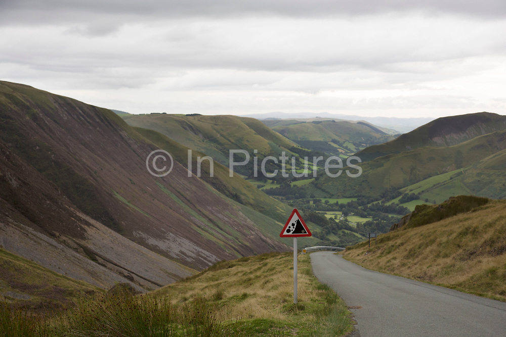 View along a valley in the Cambrian Mountains from a point of natural beauty towards Llanymawddwy. Wales, UK. A warning sign showing that there may be falling rocks in the area.