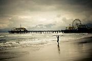 A surfer heads to the water by the Santa Monica Pier, Santa Monica Beach, California.