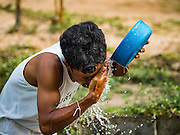 10 MAY 2016 - TA TUM, SURIN, THAILAND: A man washes his face at the cistern people use for bathing at the artesian well in Ta Tum, Surin, Thailand. The well is the most important source of drinking water for thousands of people in the communities surrounding it.  In the past many of the people had domestic water piped to their homes or from wells in their villages but those water sources have dried up because of the drought in Thailand. Thailand is in the midst of its worst drought in more than 50 years. The government has asked farmers to delay planting their rice until the rains start, which is expected to be in June. The drought is expected to cut Thai rice production and limit exports of Thai rice. The drought, caused by a very strong El Nino weather pattern is cutting production in the world's top three rice exporting countries:  India, Thailand and Vietnam. Rice prices in markets in Thailand and neighboring Cambodia are starting to creep up.    PHOTO BY JACK KURTZ