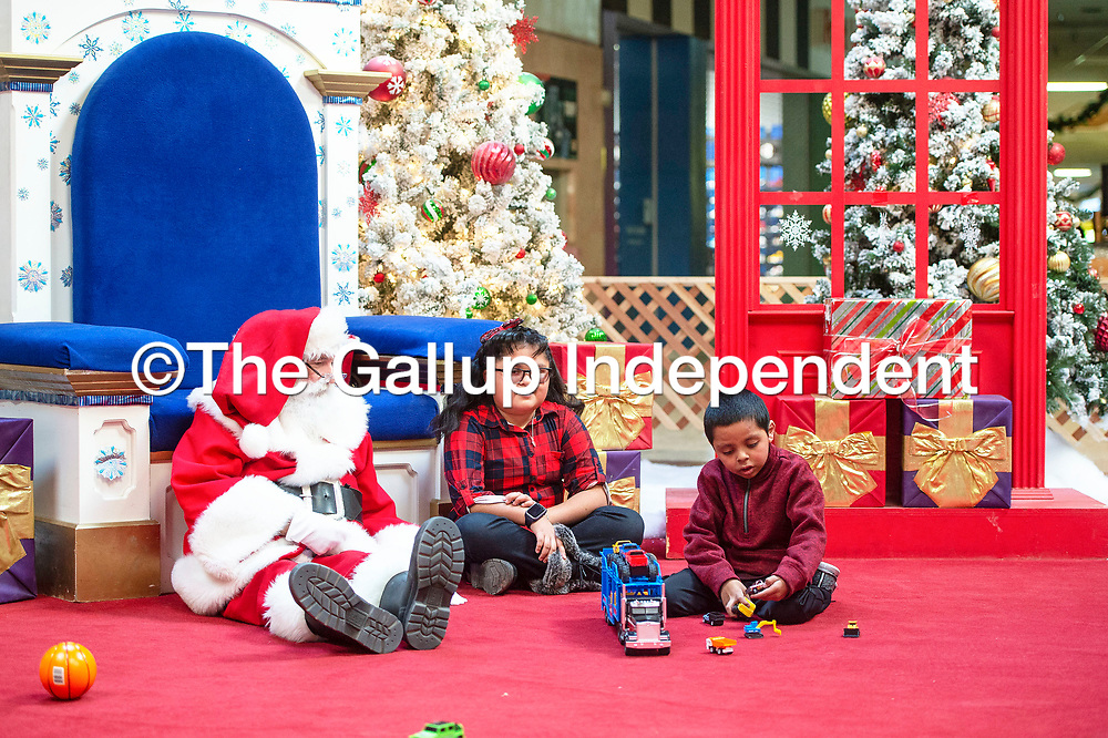 Siblings Samone, 10, center, and Ramone Montelongo, 8, right, visit with Santa Claus, Sunday Dec. 9 at Rio West Mall before the mall opens to the public. Rio West Mall partnered with Autism Speaks to host it's first Santa Cares event in Gallup, an event for kids with special needs.