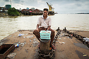 18 JUNE 2013 - YANGON, MYANMAR:   A vendor sits on a freighter pier waiting for customers.     PHOTO BY JACK KURTZ
