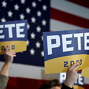Supporters of Democratic presidential candidate Pete Buttigieg hold up signs before a town hall at the Courtyard Hotel in Ankeny, Iowa on Thursday, January 30, 2020.