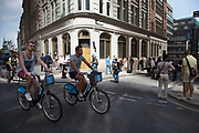 """London, UK. Wednesday 4th September 2013. Two cyclists on Boris Bikes pass the light beam. Urgent action in planned to """"cover up"""" the Walkie Talkie skyscraper in the City after sunlight reflected from the building melted a car on the streets below. Temperatures have been measured in excess of 50 degrees C, and as much as 70 degrees at it's peak. The 525ft building has been renamed the """"Walkie Scorchie"""" after its distinctive concave surfaces reflected a dazzling beam of light which has caused extensive damage to nearby buildings."""