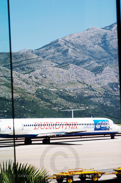 An aircraft airplane plane from Dubrovnik Airline, at the Dubrovnik airport against a backdrop of the steep impressive mountains. Dubrovnik, new city. Dalmatian Coast, Croatia, Europe.