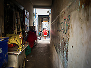 09 DECEMBER 2014 - THONBURI, BANGKOK, THAILAND:  A woman walks through an alley in a market in the Thonburi section of Bangkok.   PHOTO BY JACK KURTZ