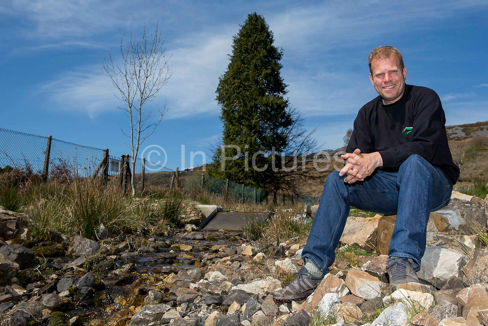 Chris Blake of The Green Valleys sitting by the entry point to the Abercrave Farm 15kW hydro power plant on the Brecon Beacons, Wales.