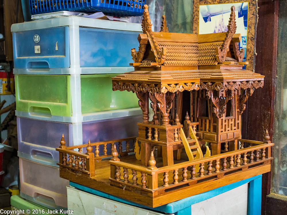02 NOVEMBER 2016 - BANGKOK, THAILAND:  A completed spirit house in the workshop awaits shipping. There used to be 10 families making traditional spirit houses out of teak wood in Ban Fuen, a community near Wat Suttharam in the Khlong San district of Bangkok. The area has been gentrified and many of the spirit house makers have moved out, their traditional wooden Thai houses replaced by modern apartments. Now there is just one family making the elaborate spirit houses. The spirit houses are made by hand. It takes three days to make a small one and up to three weeks to make a large one. Prices start at about $90 (US) for a small one. The largest, most elaborate ones can cost over $1,000 (US). Almost every home and most commercial buildings in Thailand have a spirit house, which is a shrine to the protective spirit of a the land. Spirit houses are also common in Burma, Cambodia, and Laos.       PHOTO BY JACK KURTZ