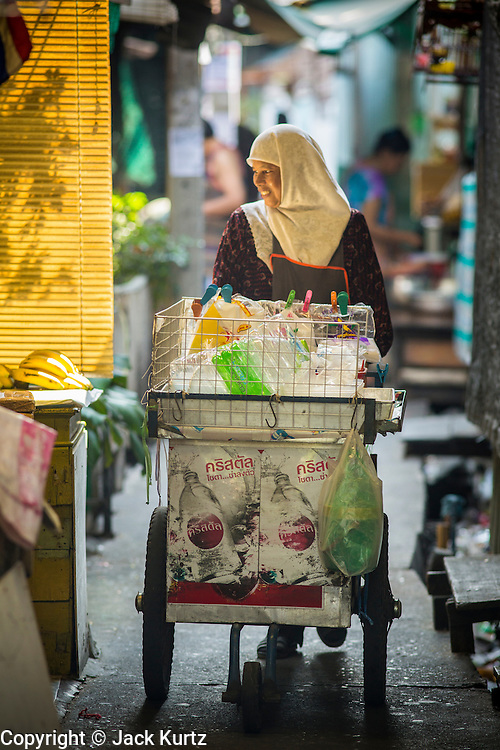 """10 JANUARY 2013 - BANGKOK, THAILAND:      A Muslim woman pushes the snack cart she sells food from through the Baan Krua neighborhood in Bangkok. The Ban Krua neighborhood of Bangkok is the oldest Muslim community in Bangkok. Ban Krua was originally settled by Cham Muslims from Cambodia and Vietnam who fought on the side of the Thai King Rama I. They were given a royal grant of land east of what was then the Thai capitol at the end of the 18th century in return for their military service. The Cham Muslims were originally weavers and what is known as """"Thai Silk"""" was developed by the people in Ban Krua. Several families in the neighborhood still weave in their homes.   PHOTO BY JACK KURTZ"""