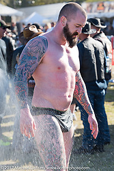 Big Joe Lingley of Live Free Cycle, Hampton, NH gets sprayed off after winning his Coleslaw Wrestling match match against long standing champion Heather Spears at the Cabbage Patch during Daytona Bike Week. (Joe is reported to be the first male to wrestle in the slaw.) New Smyrna Beach, FL. USA. Wednesday March 15, 2017. Photography ©2017 Michael Lichter.
