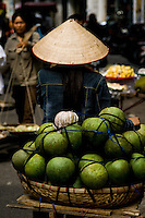 A pomelo vendor wearing a conical hat wheels her bicycle along the streets of the old quarter in Hanoi.