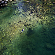 A kayaker takes a break and enjoys a swim in the crystal clear waters of a sheltered lagoon in the Abel Tasman National Park., South Island, New Zealand, The Abel Tasman National Park at the top of the South Island was established in 1942. it is renowned for its golden beaches, sculptured granite cliffs, native wildlife encounters and beautiful scenery..A number of kayaking companies run guided tours from Marahau, Kaiteriteri and Golden Bay. Abel Tasman National Park, South Island, New Zealand. 5th.February 2011, Photo Tim Clayton.