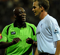 Photo: Ed Godden.<br /> Portsmouth v Bolton Wanderers. The Barclays Premiership. 25/09/2006. Referee Uriah Rennie has a laugh with Bolton's Kevin Davies (R).