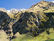 A waterfall flows down a rugged mountainside near Treble Cone Ski Area, Harris Mountains, near Wanaka, New Zealand