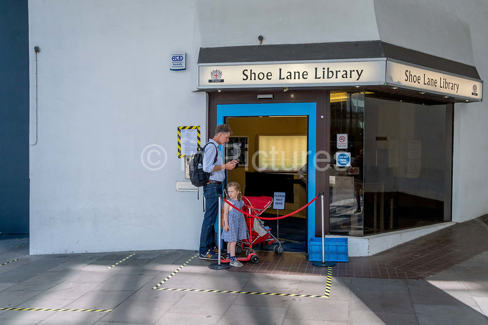 A father and his young children wait to safely enter Shoe Lane Library during the Coronavirus pandemic in the City of London, the capitals financial district, on 6th August 2020, in London, England.