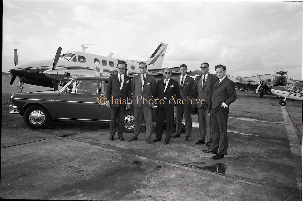 25/06/1965<br /> 06/25/1965<br /> 25 June 1965<br /> Arrival of Dr Carl H. Hahn of Volkswagen at Dublin Airport.<br /> Dr. Hahn, Sales and Service Director, Volkswagenwerke, A.G., Germany, arrived in Ireland on the company plane. He was President of Volkswagen of America. He had recently returned to Wolfsburg and was visiting Ireland as part of a brief European tour to familiarise himself with local conditions. Image shows Dr Hahn (2nd from left. in front of his Beechcraft Kingair being greeted by Mr. Stephen O'Flaherty (3rd from left); Mr. Michael P. O'Flaherty (on left), Chairman Volkswagen Distributers Ltd. and Mr. Dermod Ryan, General Manager Volkswagen Distributers Ltd. (on right?). Also present were Mr. E. Schneider and Mr. U. (?) P. Kiesewetter, Factory Delegates for North West Europe. Car appears to be a Volkswagen Type 3.