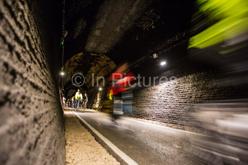 Cyclists riding through the restored Devonshire Tunnel which is part of the Two Tunnels Greenway near Bath, Somerset, England, United Kingdom on 6th April 2013.  The tunnel is 407 meters long and has been restored so it is accessible by foot, cycle or wheelchair and well light throughout.  The tunnel was previously part of a main railway line, the walls are blackened with a thick crust of soot from engine exhaust, while a strip in the roof is blasted clean by that same exhaust.  The tunnel is stone-lined throughout and on a curved and falling 1:50 gradient.  The tunnel is part of a 13-mile route and was restored by Sustrans in partnership with Bath and North East Somerset Council.  The opening of the route was attended by hundreds of cyclists and pedestrians to celebrate the new access to beautiful Somerset country-side.