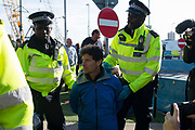 Former police officer John Curren age 49,  is arrested as climate change protest group Extinction Rebellion stage a protest at London City Airport during day four of two weeks of planned demonstrations on 10th October, 2019 in London, Untited Kingdom. Extinction Rebellion is demanding that governments drastically cut carbon emissions.