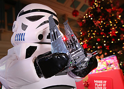 © Licensed to London News Pictures. 04/11/2015. London, UK. A Star Wars storm trooper holds a Lego Kylo Ren Command Shuttle at the Dream Toys Christmas event. Photo credit: Peter Macdiarmid/LNP