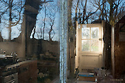 We stumbled across what we thought was a derelict cottage in the middle of woodland down a tiny track. <br /> <br /> Evening sunlight was pouring through a window beyond, and there was a reflection of the sky and trees in the front windows. I went up to the window &  was shocked to discover signs of habitation. There was even a calendar from 2015 on the wall, yet still I suspected that the place had just been deserted. I took this one image because of the beautiful light and sense of time passing, melancholy almost but imbued with such positive afternoon sunshine. <br /> <br /> It was only then that I heard a car pull up behind us. The very jovial driver was the landowner, and he told us that someone does indeed live there. The tenant is a 75 year old man who refuses to connect any power to the house, even though all the faciities are there. He only has a gas bottle to power his ancient stove. <br /> <br /> This old man has a tiny garden plot over a mile away on a steep cliff side, and he walks there regulalrly to tend his vegetagbles. He has an old car, but that is one of his only links wih modern'ish technology. <br /> <br /> The landowner is in no hurry to move the old gentleman on, and it seems he will see the end of his days in this ancient farmyard cottage, almost off the grid, and I hope deeply happy because of it. <br /> <br /> Next time I'm down, I'd love to photograph the old man himself, if he'd be happy for me to do so. What a character he must be.