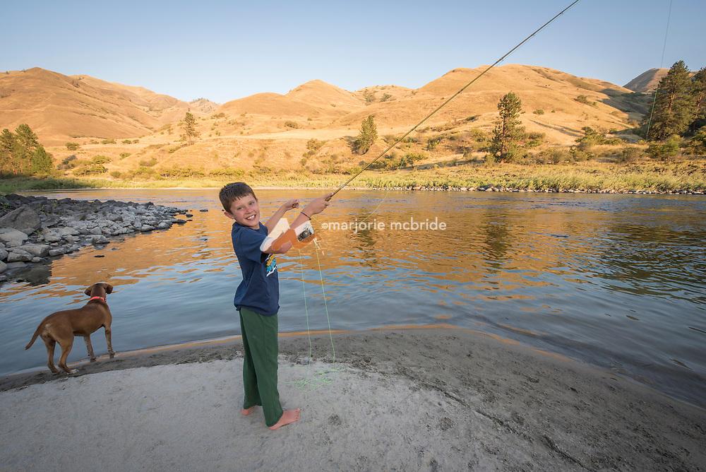 Little boy and his dog fishing at camp while rafting the Main Lower Salmon River, Hammer Creek to Hellar Bar, Idaho.