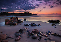 Colorful clouds light up at sunrise along the rocky coastline of Cape Breton island, Nova Scotia, Canada