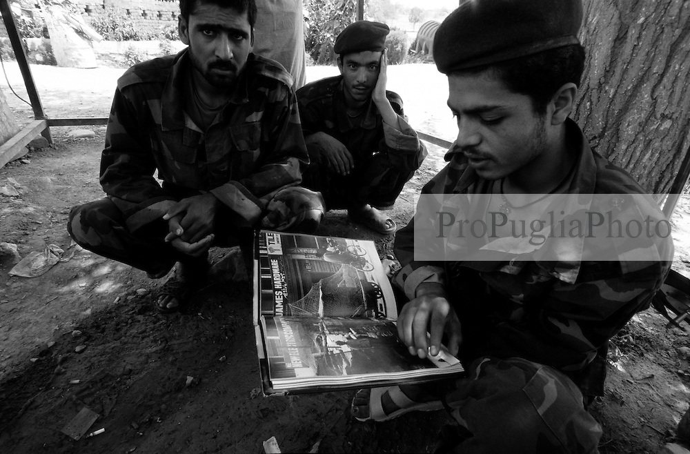 AFGHANISTAN, KHOST 11 AUGUST 2005...Soldiers of the Afghan National Army (ANA), wearing camouflage uniforms, leaf through a photographic book on Kashmir..