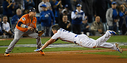 November 1, 2017 - California, United States - Los Angeles Dodgers shortstop Corey Seager #5 dives back to first base while Houston Astros first baseman Yuli Gurriel #10 waits for the throw. Seager thought about tring to stretch a single into a double, but had second thoughts in the 3rd inning. Los Angeles Dodgers played the Houston Astros in game 7 of the World Series at Dodger Stadium in Los Angeles, CA 11/1/2017  (Credit Image: © John Mccopy/Los Angeles Daily News via ZUMA Wire)