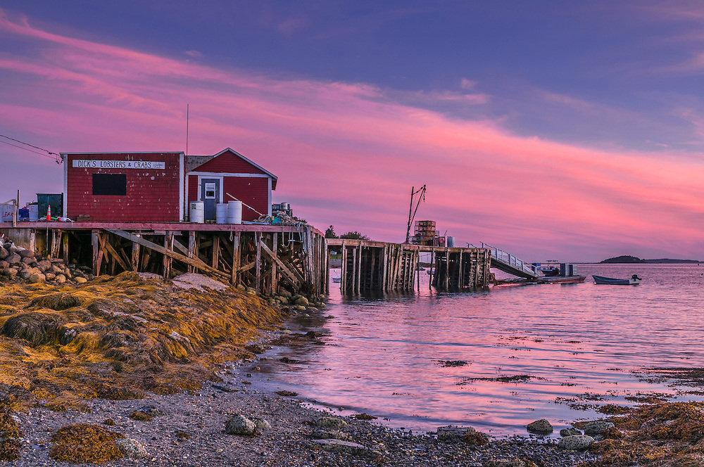 Pink dusk colors in sky and water, with lobster shack on piers, South Harpswell, ME