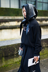 Margaret Zhang wears a pleated skirt, a hoodie sweater VLTN, a black leather oversized hood, outside Valentino, during Paris Fashion Week Womenswear Fall/Winter 2018/2019, on March 4, 2018 in Paris, France.  (Photo by Nataliya Petrova/NurPhoto/Sipa USA)