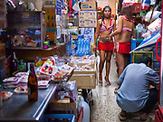 "12 JULY 2011 - BANGKOK, THAILAND:  Waitresses and dancers at a bar on Soi Cowboy in Bangkok look for drinks in a convenience store across the street from their bar. Soi Cowboy is a ""red light"" district in Bangkok and home to several brothels and ""short time"" hotels that charge by the hour for their rooms. Prostitution in Thailand is illegal, although in practice it is tolerated and partly regulated. Prostitution is practiced openly throughout the country. The number of prostitutes is difficult to determine, estimates vary widely. Since the Vietnam War, Thailand has gained international notoriety among travelers from many countries as a sex tourism destination. One estimate published in 2003 placed the trade at US$ 4.3 billion per year or about three percent of the Thai economy. It has been suggested that at least 10% of tourist dollars may be spent on the sex trade. According to a 2001 report by the World Health Organisation: ""There are between 150,000 and 200,000 sex workers (in Thailand).""  PHOTO BY JACK KURTZ"