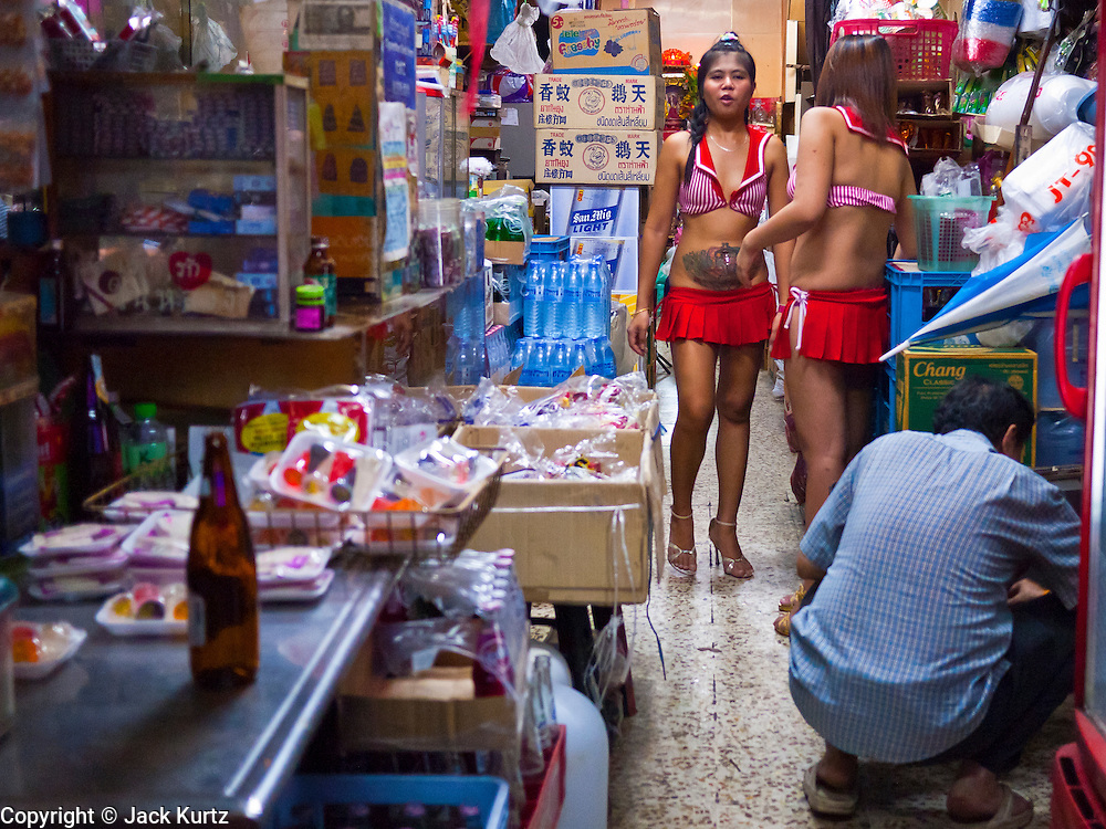 """12 JULY 2011 - BANGKOK, THAILAND:  Waitresses and dancers at a bar on Soi Cowboy in Bangkok look for drinks in a convenience store across the street from their bar. Soi Cowboy is a """"red light"""" district in Bangkok and home to several brothels and """"short time"""" hotels that charge by the hour for their rooms. Prostitution in Thailand is illegal, although in practice it is tolerated and partly regulated. Prostitution is practiced openly throughout the country. The number of prostitutes is difficult to determine, estimates vary widely. Since the Vietnam War, Thailand has gained international notoriety among travelers from many countries as a sex tourism destination. One estimate published in 2003 placed the trade at US$ 4.3 billion per year or about three percent of the Thai economy. It has been suggested that at least 10% of tourist dollars may be spent on the sex trade. According to a 2001 report by the World Health Organisation: """"There are between 150,000 and 200,000 sex workers (in Thailand).""""  PHOTO BY JACK KURTZ"""