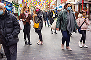 Lantern decorations for Chinese New Year Festival and people wearing face masks during the 2020 pandemic in China Town London England UK