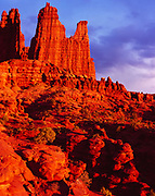 Sunset illuminating the Fisher Towers, erosional spires capped with harder Moenkopi Formation sandstone with softer Cutler Formation sandstones, mudstones and conglomerate below, Utah.